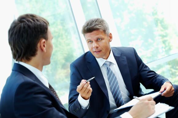 Imagem de homem argumentando para o outro, representando uma reunião de justificativa do investimento em um projeto de ERP.