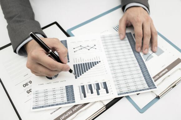 Gráficos sendo analisados pelas mãos de um profissional, referindo-se ao tema do texto que é sobre o aumento dos custos de ERP e os fatores que levam a essa consequência.