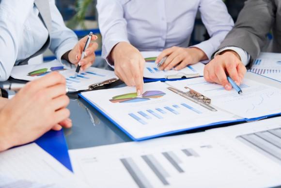 Equipe analisando gráficos, representando os fatores de sucesso de uma implantação de ERP, como o planejamento e a análise de métricas.