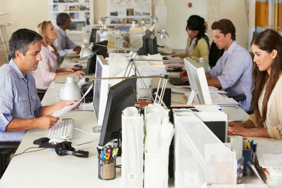 Profissionais trabalhando em seus computadores em um escritório, representando a operação de um centro de serviços compartilhados.