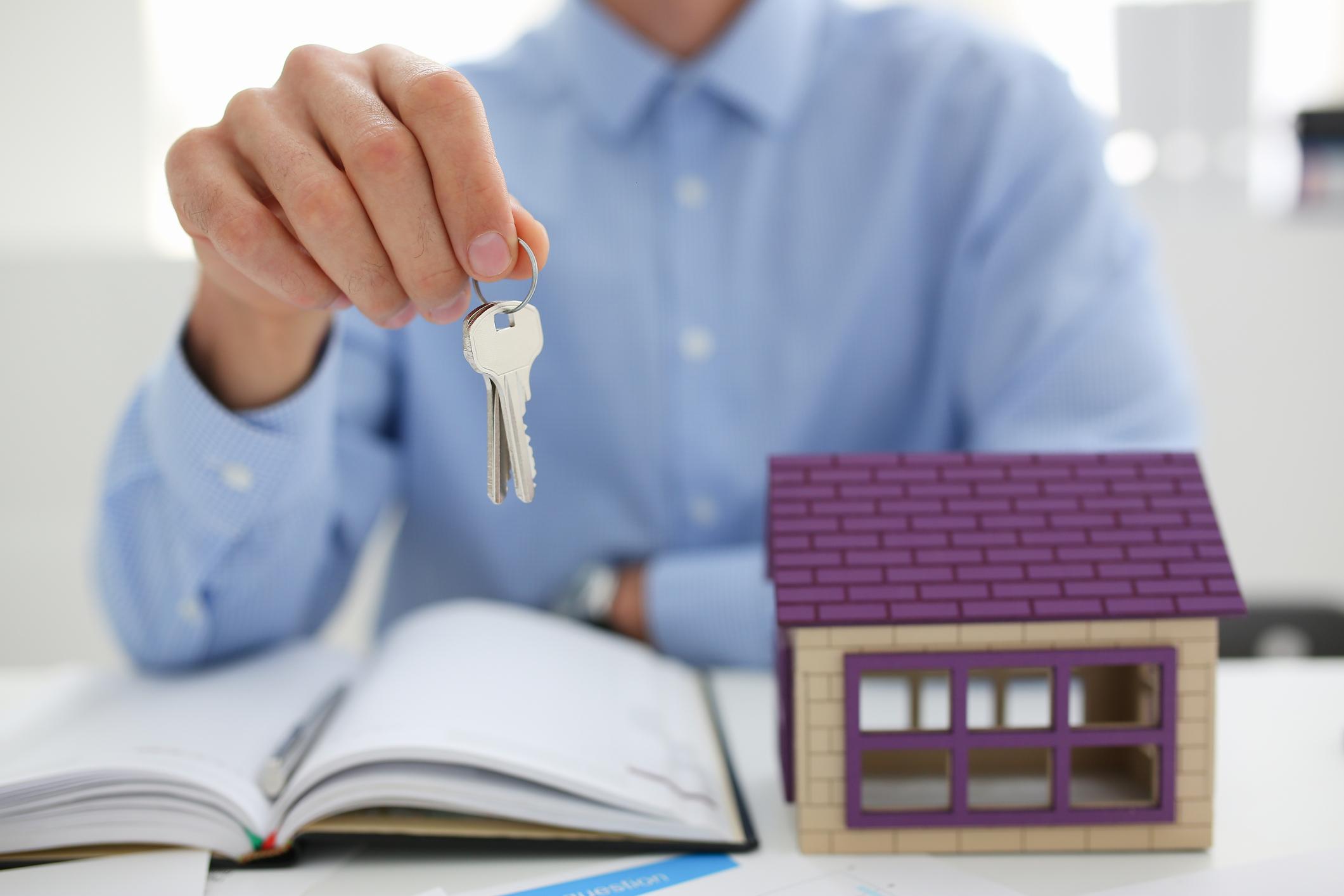 Homem de camisa azul segurando chaves com cotovelo apoiado sobre livro aberto ao lado de uma maquete de casa encima de uma mesa.